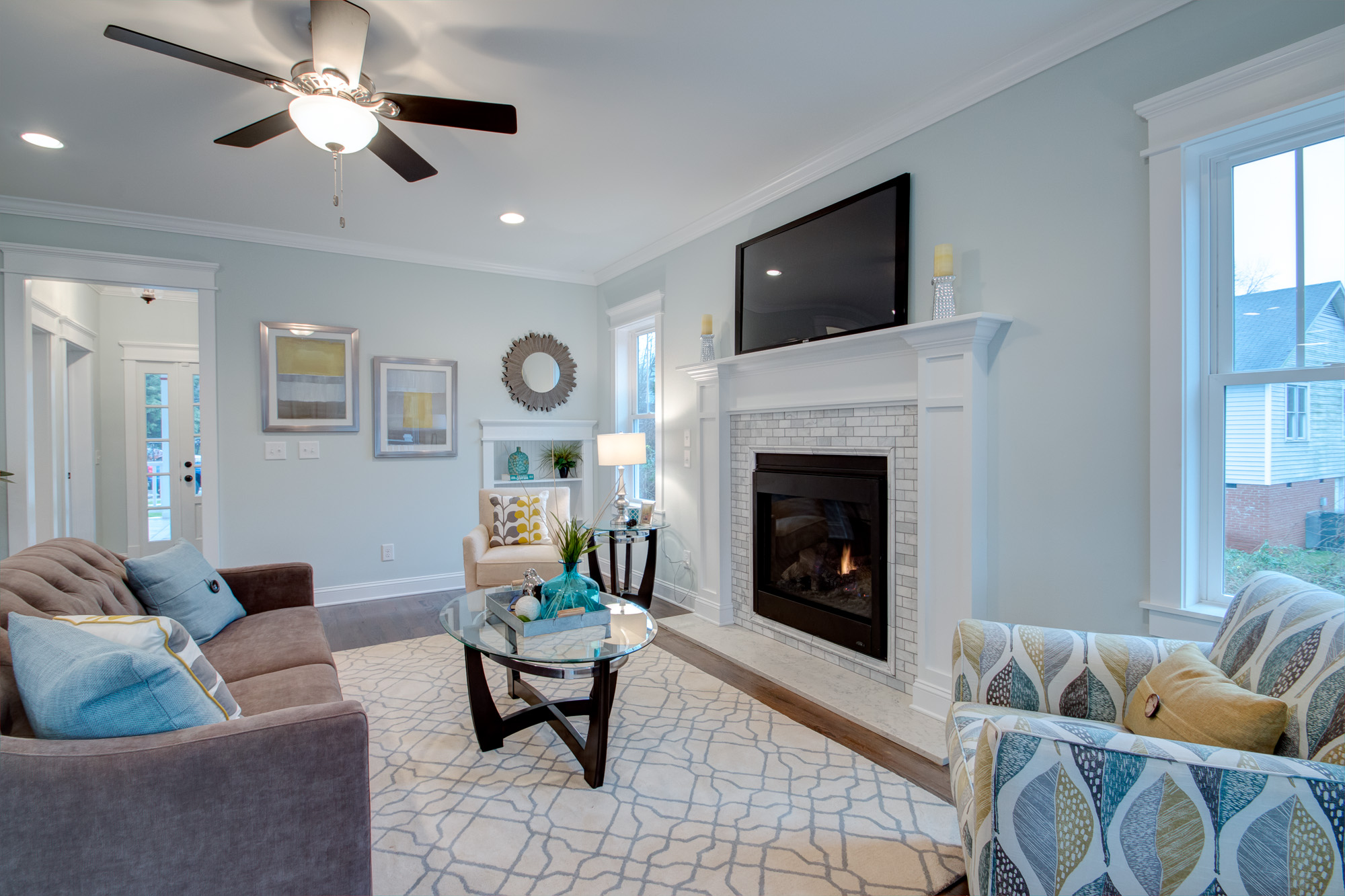 Craftsman living room with a marble tile fireplace, dark hardwood floors, and pale blue, grey walls.