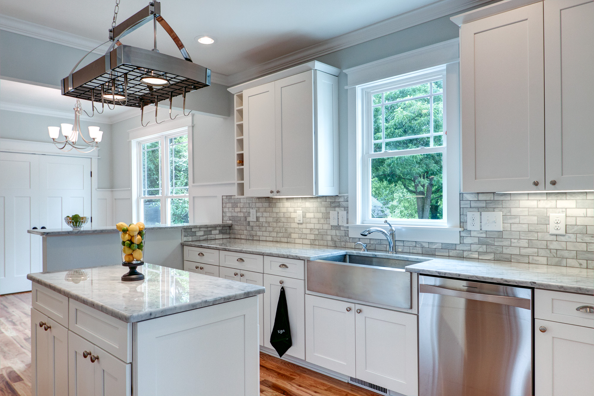 A modern farmhouse kitchen featuring clean white cabinetry with marble counter tops and stainless steel farmhouse sink.